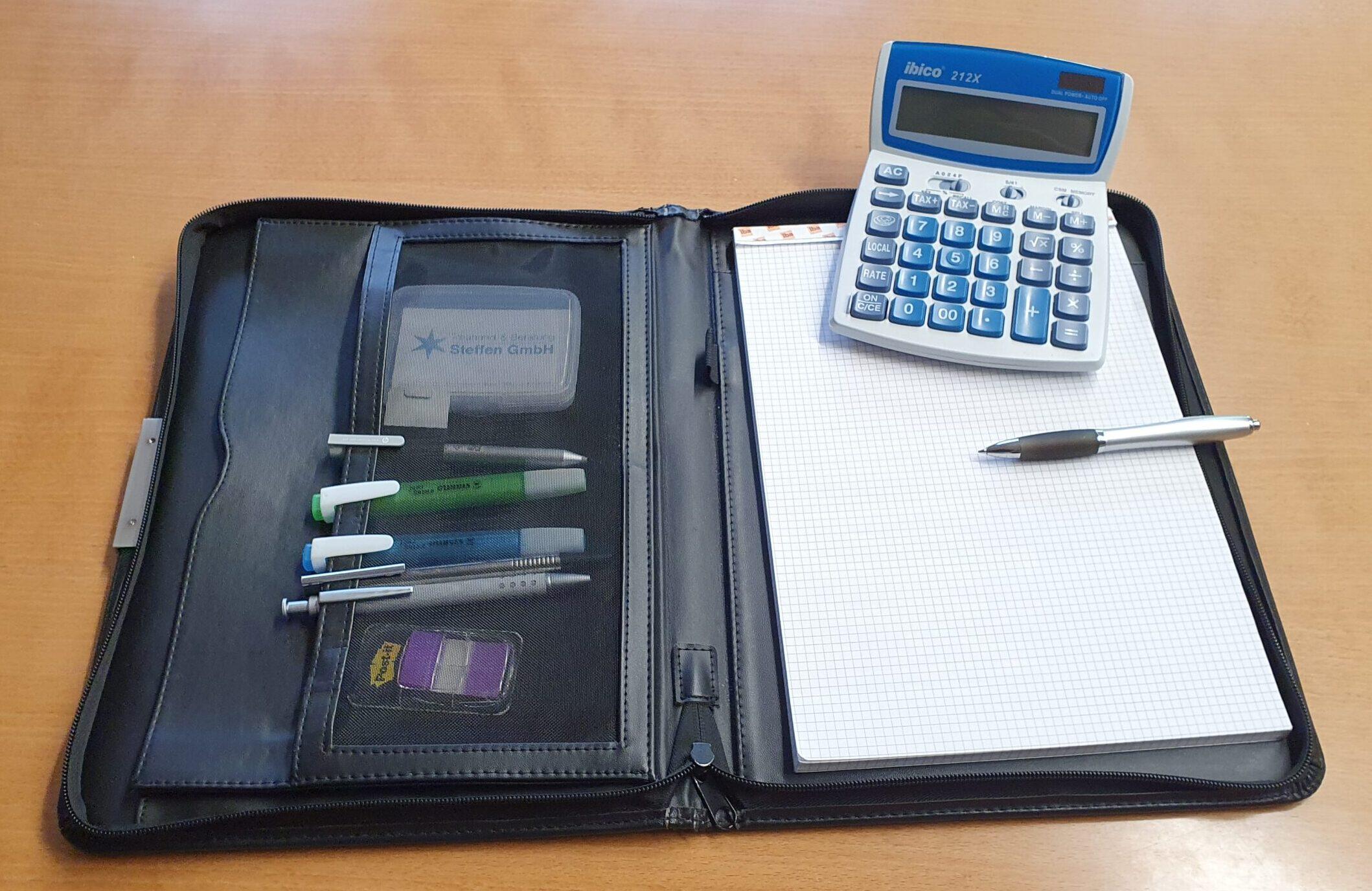 Aktenmappe mit Rechner und Kugelschreiber